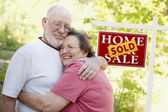 Senior Couple in Front of Sold Real Estate Sign — Stock Photo