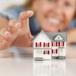 Smiling Woman Reaching for Model House on White — Stock Photo
