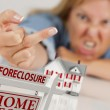 Woman Flipping The Bird Behind Model Home and Foreclosure Sign — Stock Photo #5720707