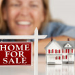 Smiling Woman Behind Real Estate Sign House on a White Surface — Stock Photo #5720710