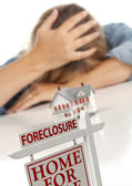 Woman, Head in Hand Behind Model Home and Foreclosure Sign — Stock Photo
