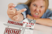 Woman Flipping The Bird Behind Model Home and Foreclosure Sign — Stock Photo
