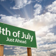 4th of July Green Road Sign Against Clouds - Stock Photo