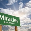 Miracles Green Road Sign Against Clouds - Stock Photo