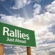 Rallies Green Road Sign Against Clouds - Stock Photo