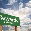 Rewards Green Road Sign Against Clouds - Stock Photo