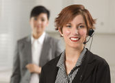 Pretty Red Haired Businesswoman with Headset in Office — Stock Photo