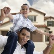 Hispanic Father and Son in Front of House - Stock Photo