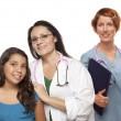 spansktalande kvinnliga läkare med barn patient och kollega — Stockfoto