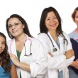Hispanic Female Doctor with Child Patient and Colleagues Behind — Stockfoto #6583499
