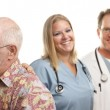 Senior Couple with Medical Doctors or Nurses Behind — Stock Photo