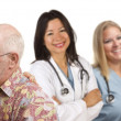 Senior Couple with Medical Doctors or Nurses Behind - Stock Photo