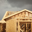 Home Construction Framing with Ominous Clouds - Stock Photo