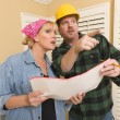 Royalty-Free Stock Photo: Contractor in Hard Hat Discussing Plans with Woman