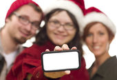 Girl with Friends and Santa Hats Holding Blank Smart Phone — Stock Photo