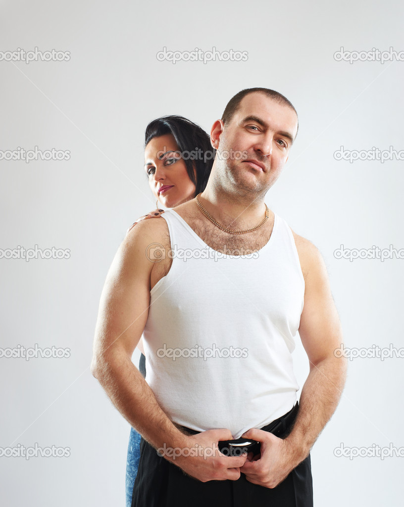 Portrait of a gangster in white tank top with his woman, studio shot  Stock Photo #5494543