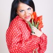 Portrait of a woman with red flowers — Stock Photo
