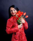 Young woman with red flowers — Стоковое фото