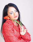 Young woman with red flowers — Stock Photo