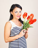Portrait of a woman with red flowers, studio shot — Stock Photo