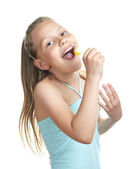 Cheerful little girl with lollipop singing — Stock Photo