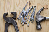 Hammer ,wrench and nails on wood background — Stock Photo