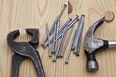 Marteau, clé et clous sur fond de bois — Photo