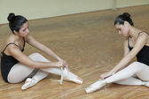 Ballerinas removing their pointe shoes — Stock Photo