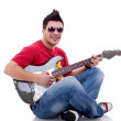 Seated guitarist playing an electric guitar — Stock Photo