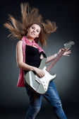 Headbanging woman guitarist playing her guitar — Stock Photo