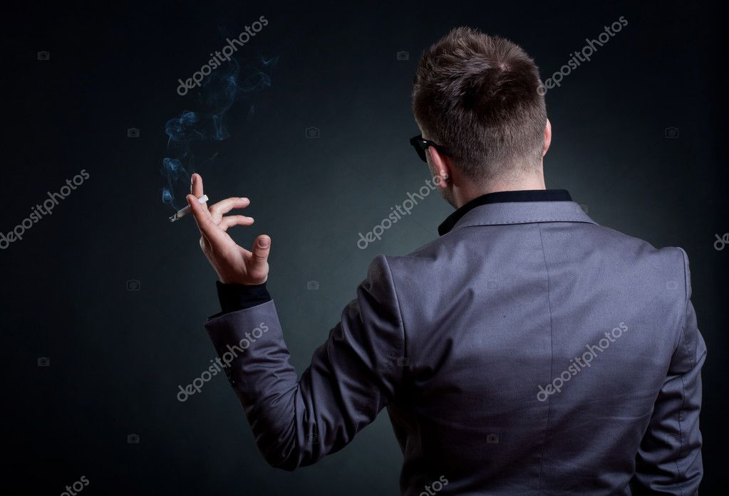 Back of a man with a cigarette in his hand, over dark background — Stock Photo #5589700