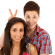 Man goofing around behind his girlfriend - Stock Photo