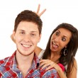 Woman goofing around behind her boyfriend - Stock Photo