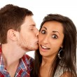 Woman kisses her boyfriend on the cheek - Stock Photo