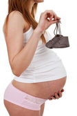 Pregnant woman holding baby shoes — Stock Photo