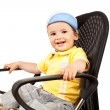 Boy sitting on a black chair - Foto Stock