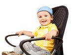 Boy sitting on a black chair — Stock Photo