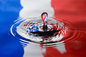 Water droplet against a French flag — 图库照片