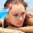 Stock Photo: Young woman on the beach with cocktail