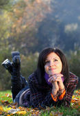 Young woman relaxing on the ground in autumn — Stock Photo