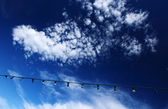 Cloudscape with lamps on wire — Stock Photo