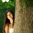 Happy young woman behind a tree — Stock Photo