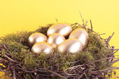Golden eggs in bird nest over yellow — Stock Photo