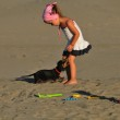 A beautiful little girl play and jump on the beach with a dog — Stock Photo