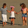Two girls and a boy playing on the beach sand — Stock Photo
