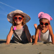 Two little girls lying on the sandy beach — Stock Photo #6610122