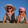 Two little girls lying on the sandy beach — Stock Photo