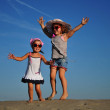 Two happy little girl jumping on the beach — Stock Photo
