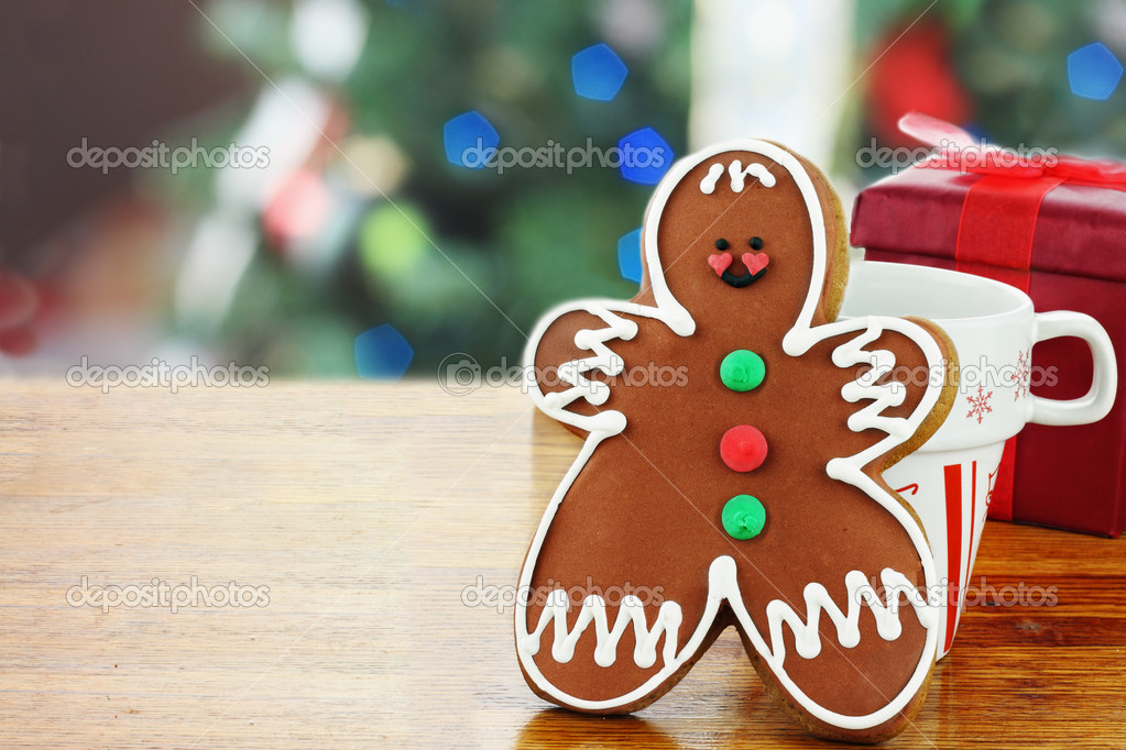 Gingerbread man cookie has been set out for Santa with a cup of milk. Christmas tree in the background. — Stock Photo #6249210
