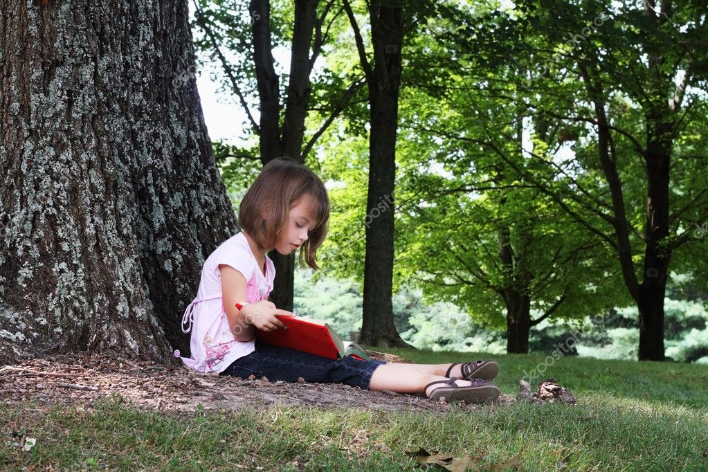Little girl sits outdoors under a large oak tree and reads a book. — Stock fotografie #6249219